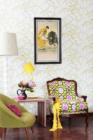 Fifties chair, bright postmodern armchair and yellow table lamp on stool against wall with floral wallpaper