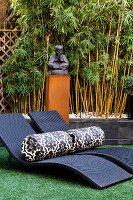 Bolsters on dark wicker sun loungers in front of statue of Buddha and stand of bamboo against wall