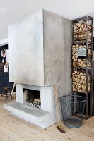 Steel shelves of firewood and concrete chimney breast with open fireplace in Scandinavian living room with pale spruce flooring