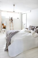 Double bed with pale grey, knitted blanket in Scandinavian bedroom with white wooden floor; decorative ladder and full-length mirror in background