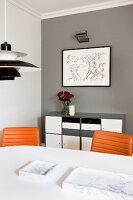 Partially visible Poulsen pendant lamp above white dining table and swivel chairs with leather covers against grey wall