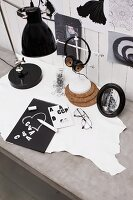 Designing a greetings cards with adhesive letters; headphones and vintage lamp on concrete-effect desk and fashion pictures on white-painted wall panelling