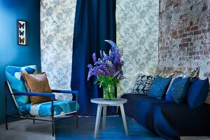 Blue painted wall, patterned wallpaper and brick wall as backdrop for blue seating area with sofa, armchair and bouquet of lupins on side table