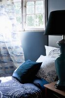 Blue-patterned pillows and blanket on bed below lattice window with curtain