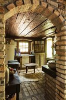 View through brick archway into rustic kitchen with dark wooden ceiling, brick floor and walls