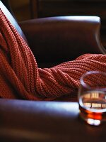 A Leather arm chair with a cable knit throw and glass of bourbon