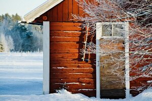 Swedish wooden cabin surrounded by snowy ground
