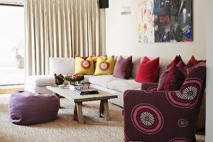 White chaise sofa with colourful scatter cushions, simple coffee table and purple beanbag on natural fibre rug