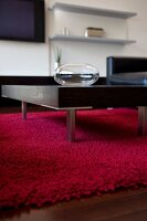 Coffee table with metal legs on red woollen rug