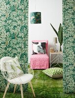 Bolts of fabric in jungle pattern as partition in front of loose-covered easy chair and side table on green carpet