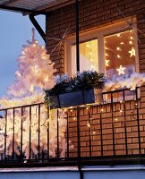 Balcony decorated for Christmas with white Christmas tree & fairy lights
