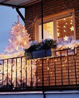 Weihnachtlich geschmückter Balkon mit weißem Tannenbaum & Lichterketten