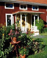 Rotes schwedisches Holzhaus mit Eingangsveranda