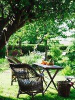 Sitzplatz mit Korbstühlen & Tischchen unter schattigem Baum im Garten
