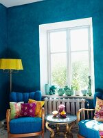 Living room with bright blue walls, antique upholstered armchairs, small side table & standard lamp