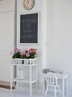Flowers on plant stand & greeting written on chalkboard in foyer