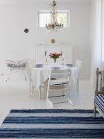 Esszimmer in schwedischem Stil in weiss & blau mit gedecktem Tisch & Kronleuchter