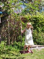 Kleines Mädchen steht auf Schaukel im Garten