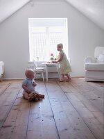 Kleines Mädchen & Kleinkind spielen auf ausgebautem Dachboden