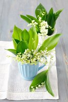 Lily of the valley in ceramic mugs on linen cloth