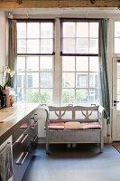 Rustic bench below lattice window next to modern kitchen counter