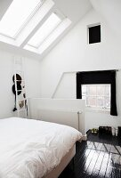 Bed with white bed linen in front of half-height balustrade wall in attic room with skylight and dark wooden floor