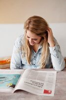 Young woman sitting at table reading a magazine