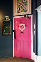 Pink door in hallway painted dark grey with framed poster and pinboard