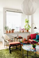 Corner of living room with stool, side tables, colourful tray, green flokati rug, spherical pendant lamp and classic, wire chair below window