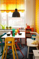 Colourful painted chairs and white bench at dining table with colourful drinking glasses; half-closed, yellow roller blind with scalloped border on window