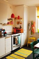White, functional fitted kitchen with yellow and blue striped rug on black floor