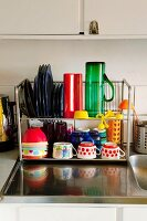 Colourful crockery on metal drying rack on stainless steel sink surround