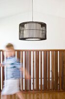 Child on gallery with balustrade of wooden rods and designer pendant lamp
