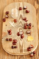 Figures made of conkers and toothpicks on chopping board
