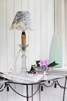 Table lamp with hand-crafted lampshade in white and blue toile de jouy fabric on metal table against wood-clad wall