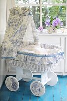 Romantic cot made from old bassinet with hand-crafted canopy in white and blue toile de jouy fabric