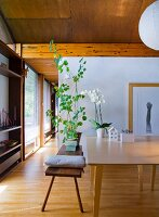 Wooden bench with cushions and potted plant next to table in open-plan interior with wooden ceiling