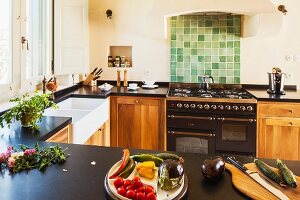 U-shaped kitchen counters - vegetables on counter opposite gas cooker with green tiled splashback and masonry extractor hood in Mediterranean kitchen