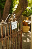Rusty garden gate with sign warning of dog in French