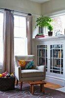 Polstersessel neben halbhohem Bücherschrank im Wohnzimmerecke