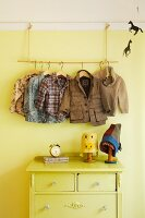 Improvised child's coat rack above chest of drawers
