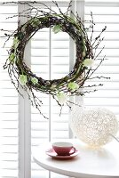 Easter wreath of willow catkins and white tulips in window and egg-shaped ornament on table