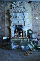 Ghost chair and Christmas arrangement on table in front of open fireplace with Greek-style, antique architectural elements in dilapidated ambiance