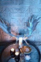 Tealights and silvered stag's antlers on tray in front of tiled wall with antique embossed motifs