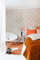 Easter atmosphere in bedroom with orange accents combined with hen-patterned wallpaper, rabbit soft toy and Easter bouquet