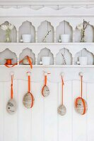Easter eggs with orange ribbons hanging from ornate kitchen shelving