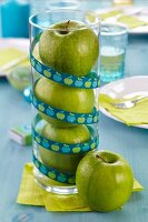Green apples stacked in glass vase decorating table