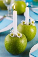 Green apples used as candlesticks decorated with chamomile flowers on dining table