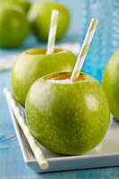 Drinking straws in green apples used as cups
