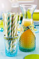 Carafe of apple juice and glass of drinking straws decorated with ribbons